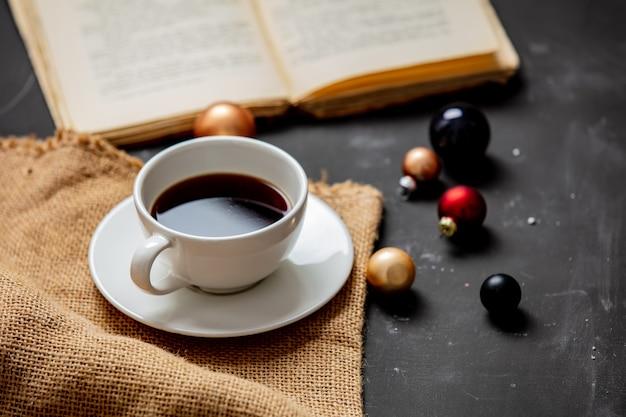 Kopje koffie en kerstballen met boek