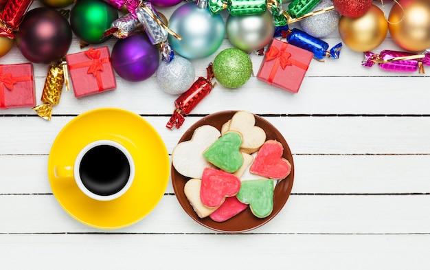Kopje koffie en koekje met kerstspeelgoed op een witte achtergrond.