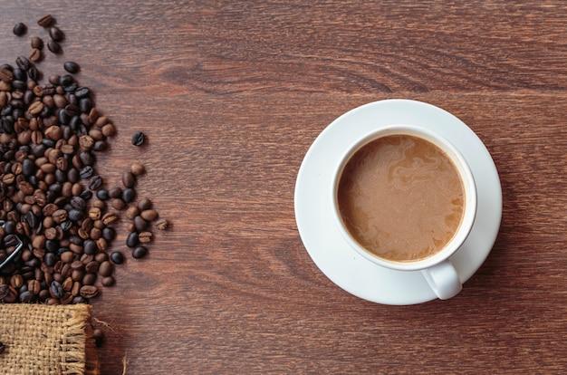 Kopje koffie en koffiebonen in een zak op bruine achtergrond, bovenaanzicht