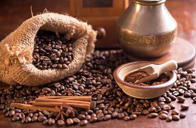 Kopje koffie en koffiebonen in een zak op donkere achtergrond, bovenaanzicht