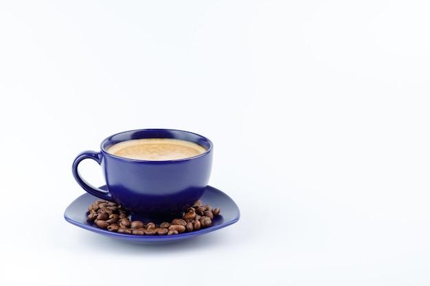 Kopje koffie en koffiebonen op een schotel op een witte achtergrond