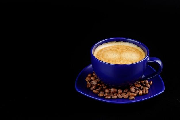 Kopje koffie en koffiebonen op een schotel op een zwarte achtergrond