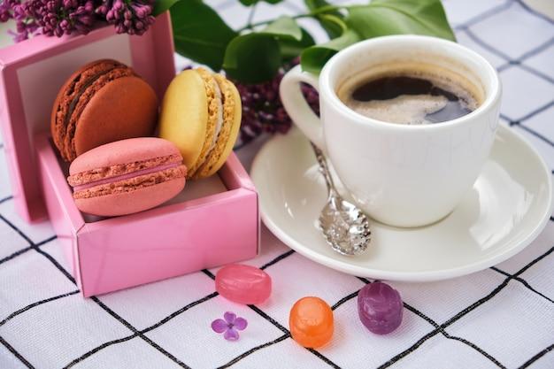 Kopje koffie en lekkere zoete macarons met karamel en gekleurde lolly's