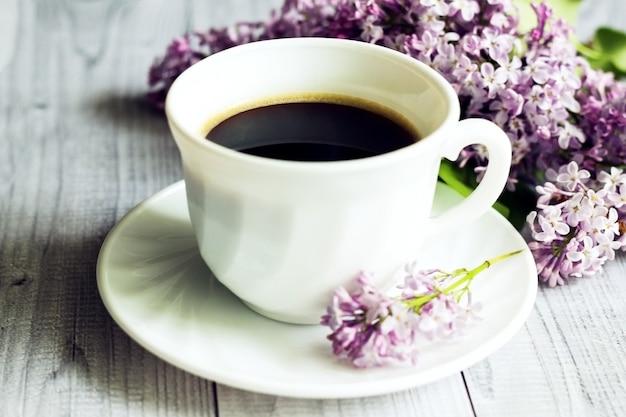 Kopje koffie en lila bloemen