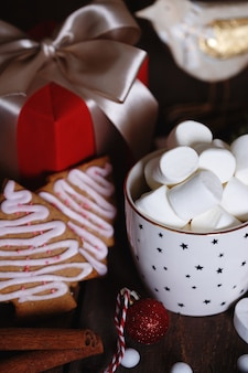 Kopje koffie en marshmallows. cadeautjes, peperkoek en kerstversiering