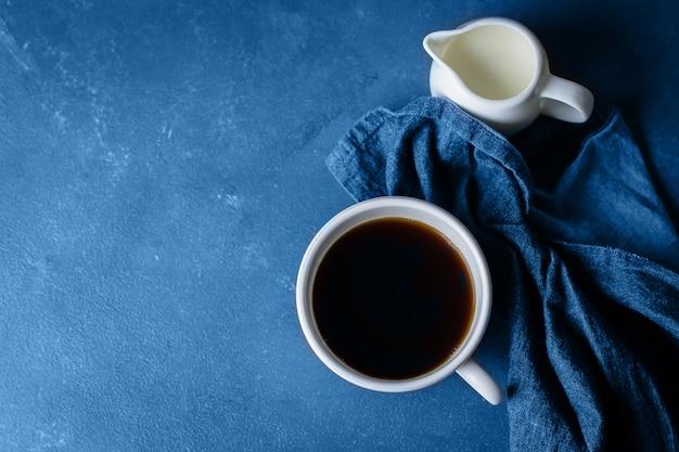 Kopje koffie en melk op blauwe stenen tafel achtergrond. kopieer ruimte, bovenaanzicht. ontbijt drankje