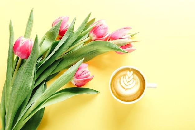 Kopje koffie en mooie roze tulpen op geel