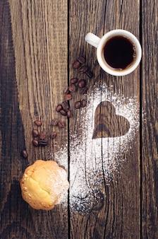 Kopje koffie en muffin op vintage houten achtergrond met hart