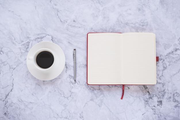 Kopje koffie en office-hulpprogramma's op witte marmeren achtergrond