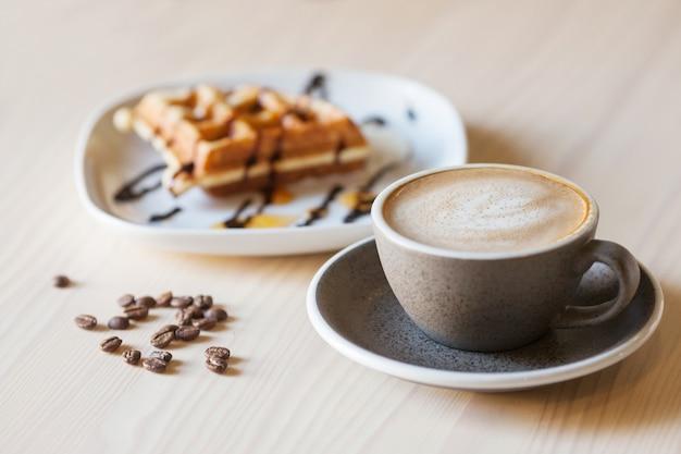 Kopje koffie en plaat van belgische wafels op lichte houten tafel