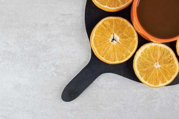 Kopje koffie en plaat van stukjes sinaasappel op een donkere bord