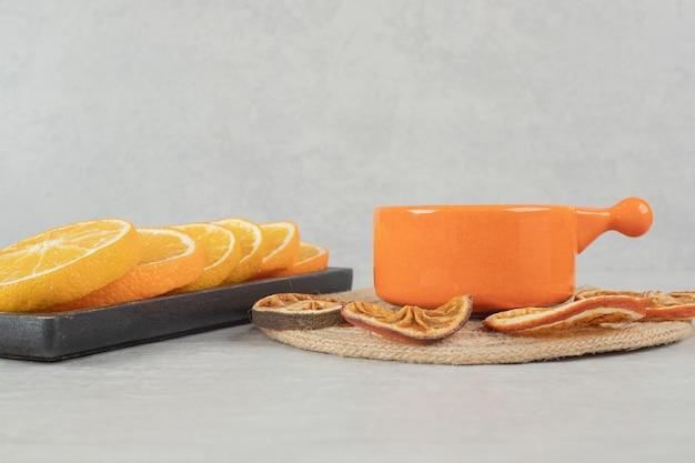 Kopje koffie en plaat van stukjes sinaasappel.