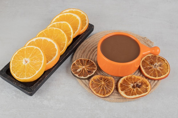 Kopje koffie en plaat van stukjes sinaasappel