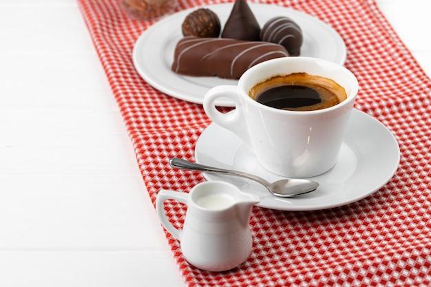 Kopje koffie en schotel met chocoladesnoepjes op houten tafel close-up
