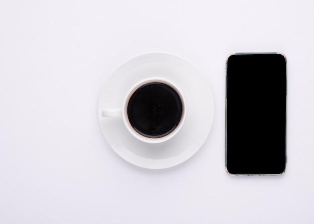 Kopje koffie en telefoon op witte achtergrond