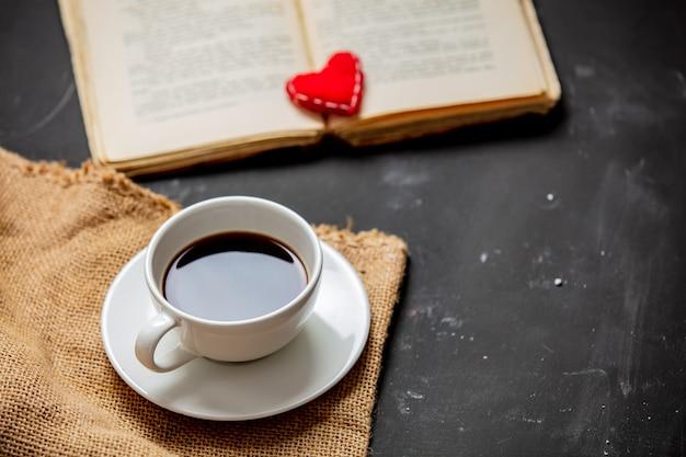 Kopje koffie en vintage boek met hart