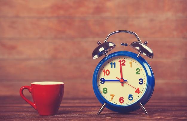 Kopje koffie en wekker op houten tafel.