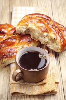 Kopje koffie en zoet broodje op een houten tafel
