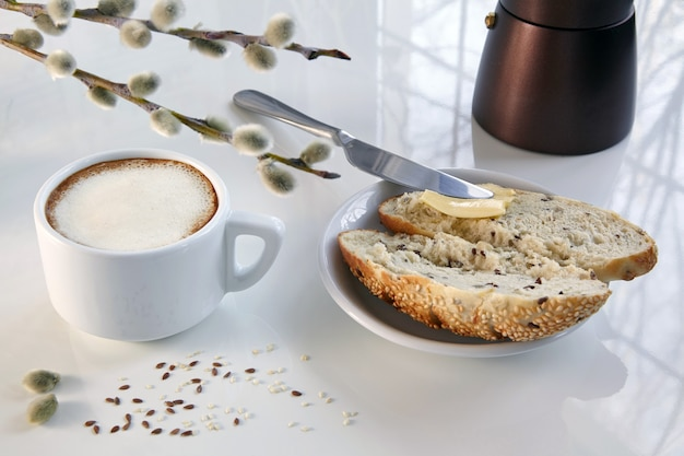 Kopje koffie, geiser koffiezetapparaat en een broodje graan met boter op een witte tafel.