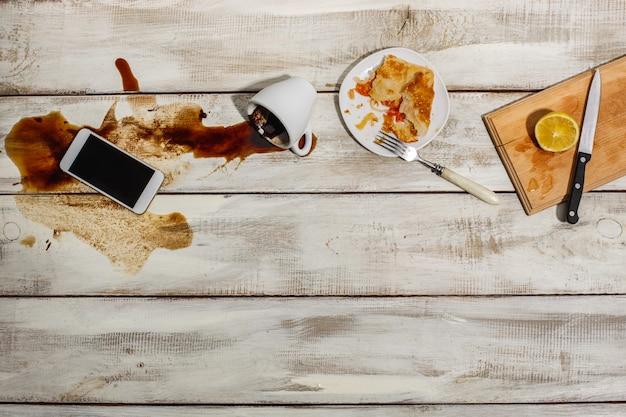 Kopje koffie gemorst op houten tafel