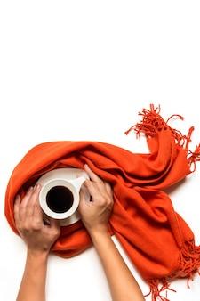Kopje koffie gewikkeld in een grijze sjaal en vrouwelijke handen op een witte achtergrond