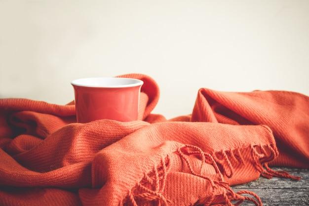 Kopje koffie gewikkeld in een oranje sjaal op een houten tafel en een grijze achtergrond.