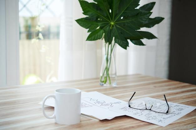 Kopje koffie, glazen en documenten met blokschema's op tafel thuis