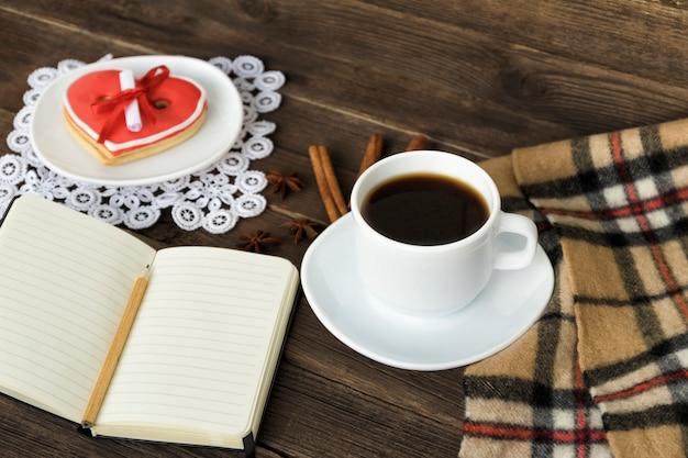 Kopje koffie, hartvormige koekjes met bericht, notitieboekje, potlood en geruite plaid