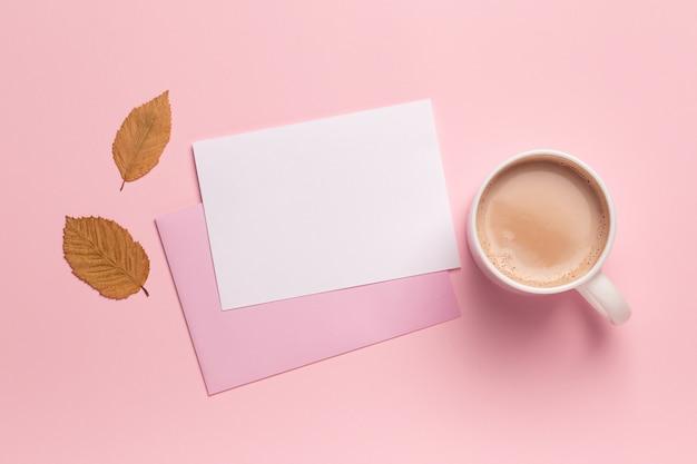 Kopje koffie, herfstbladeren en blanco pf-papier op roze pastel achtergrond, kopie ruimte