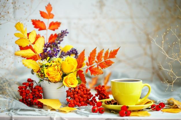 Kopje koffie, herfstbladeren en bloemen op een houten tafel
