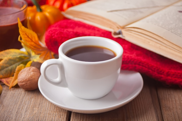 Kopje koffie, herfstbladeren, kaars, pompoen, boek en deken.