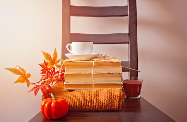 Kopje koffie, herfstbladeren, pompoen, boeken en trui op houten stoel.