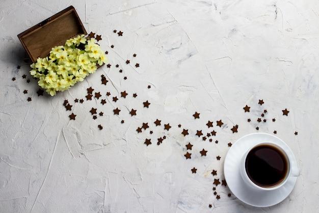 Kopje koffie, houten vintage doos met bloemen en veel kleine sterren op een lichte stenen achtergrond