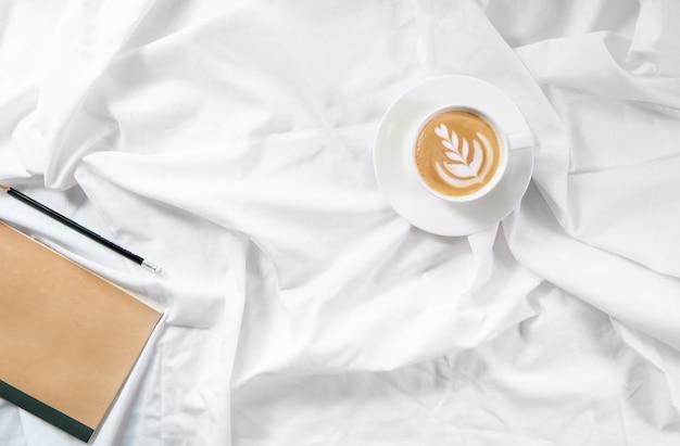 Kopje koffie in bed. ochtend flatlay in wit bed. cappuccino en ochtendroutine. het begin van de dag