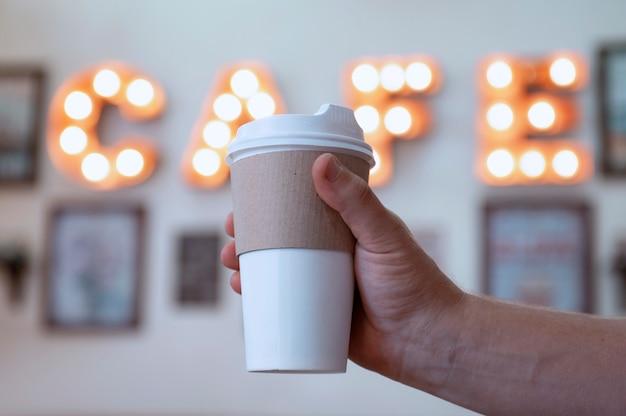 Kopje koffie in de handen van een man in een café tegen de achtergrond van een lichtgevend bord. mock-up van een kartonnen eco-mok.