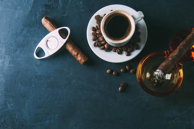 Kopje koffie, koffiebonen, asbak met sigaar op donker