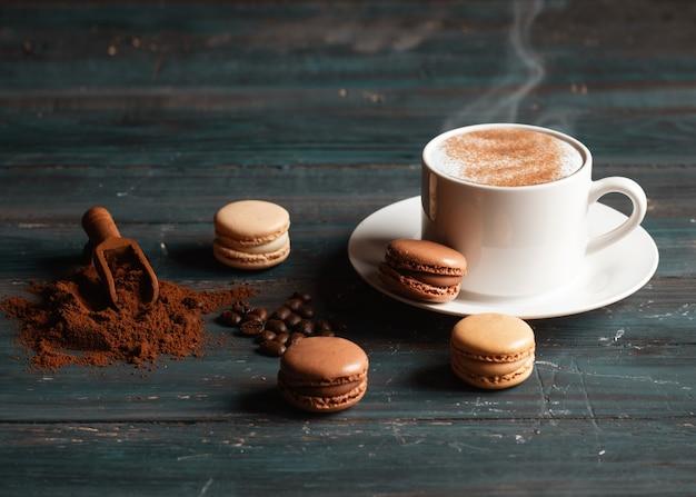 Kopje koffie, koffiebonen, gemalen koffie en bitterkoekjes op houten achtergrond