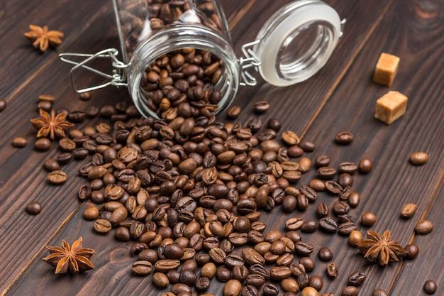 Kopje koffie, koffiebonen gestrooid uit glazen pot op tafel. kruiden steranijs en stukjes bruine suiker
