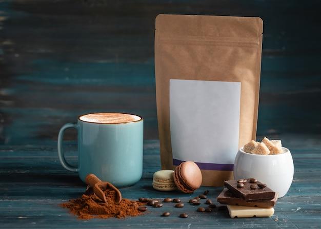 Kopje koffie, koffiebonen, suiker, ambachtelijk papier, bitterkoekjes en chocolade op houten achtergrond