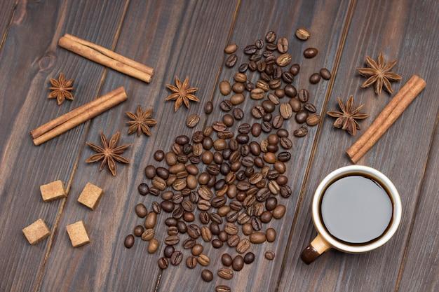 Kopje koffie. koffiebonen verspreid over tafel, steranijs, kaneelstokjes en stukjes bruine suiker