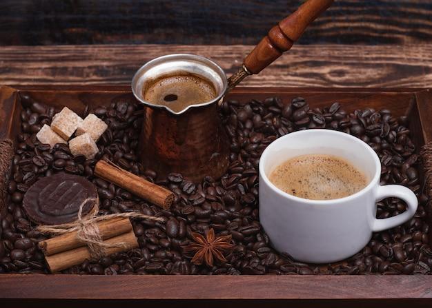 Kopje koffie, koffiepot, koekje, kaneel, anijs, suiker, koffiebonen op een houten dienblad
