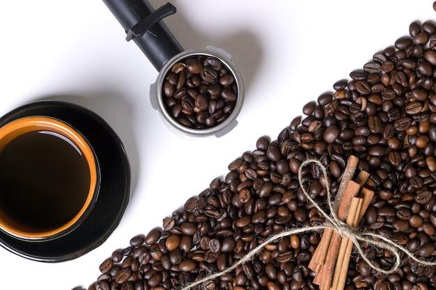 Kopje koffie, korrels koffie en kaneel op een witte achtergrond. bovenaanzicht. stilleven. ruimte kopiëren. plat leggen.