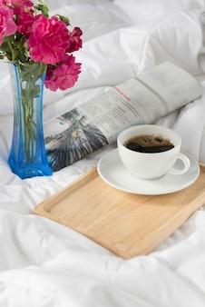 Kopje koffie, krant en roze roze bloem met houten dienblad dienen op bed