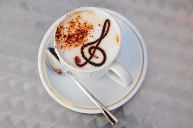 Kopje koffie latte cappuccino met roomcacaopoeder en solsleutel gemaakt van chocolade