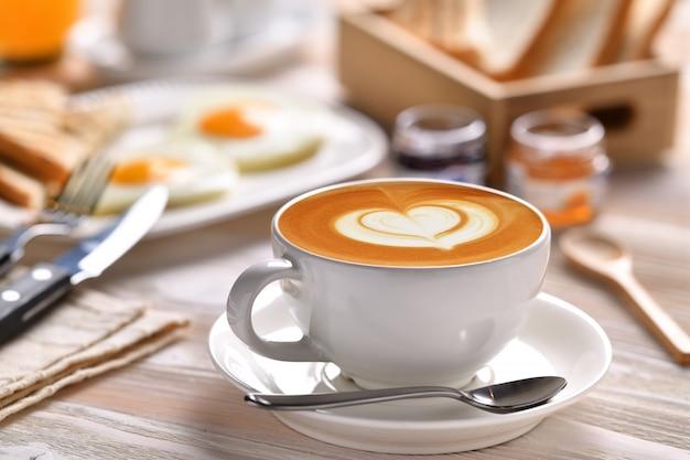 Kopje koffie latte met ontbijt op houten tafel