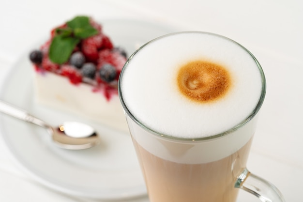 Kopje koffie latte met stuk bessen cheesecake close-up