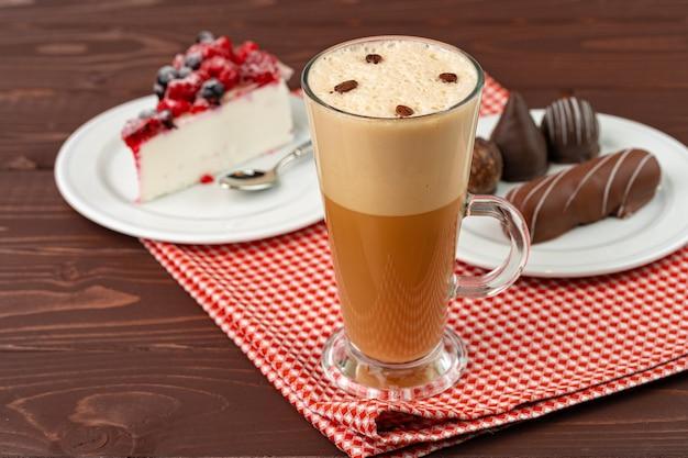 Kopje koffie latte met stuk bessen cheesecake