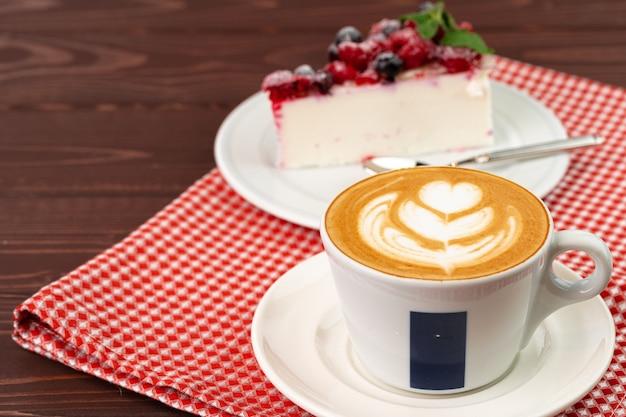 Kopje koffie latte met stuk bessenkaastaart