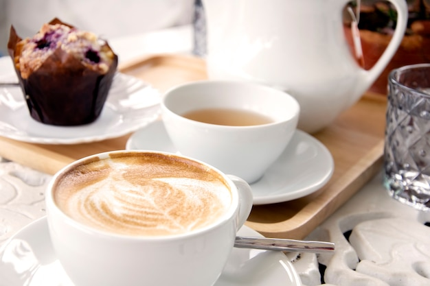 Kopje koffie latte met thee en muffins. koffie in de ochtend witte toon.