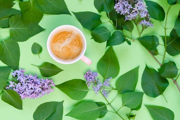 Kopje koffie, lila en groene bladeren op een groene achtergrond. bovenaanzicht